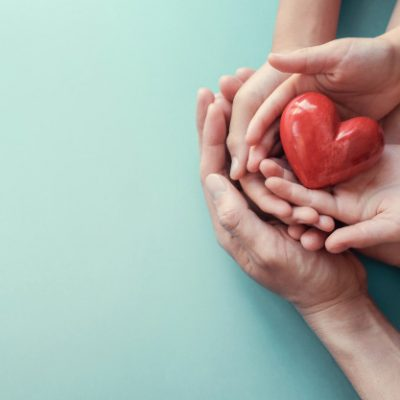 adult-child-hands-holding-red-heart-aqua-background_49149-908